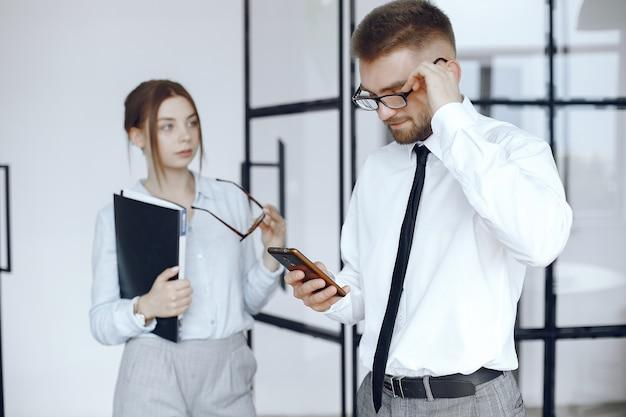 La donna tiene una cartella. partner commerciali in una riunione d'affari. l'uomo utilizza il telefono. persone con gli occhiali Foto Gratuite