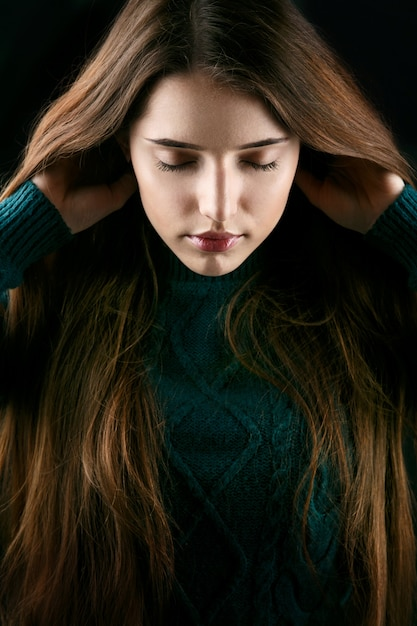 Woman holds her hair up posing in green sweater Free Photo