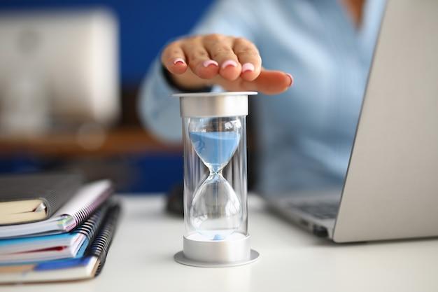 女性はオフィスのクローズアップの職場で砂時計に手をかざす Premium写真