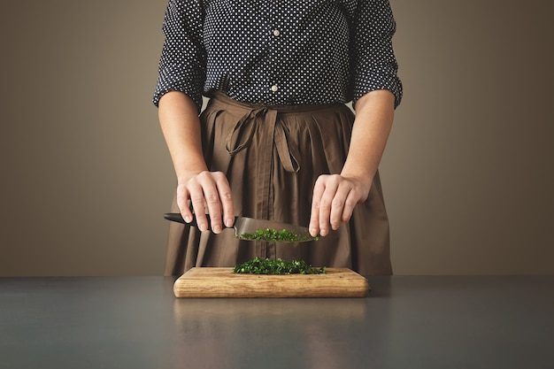 女性は、熟成した青いテーブルの上の木の板に刻んだ緑のパセリの上にナイフを持っています。 無料写真