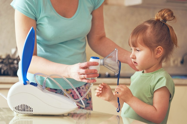 A woman holds a nebulizer mask to the little girl's face. Premium Photo