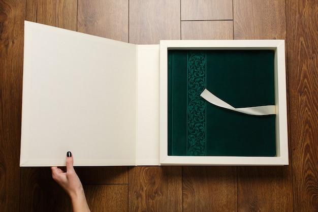 Женщина держит фотокнигу с зеленой крышкой в картонной коробке. открытый фотоальбом с замшевой обложкой Premium Фотографии