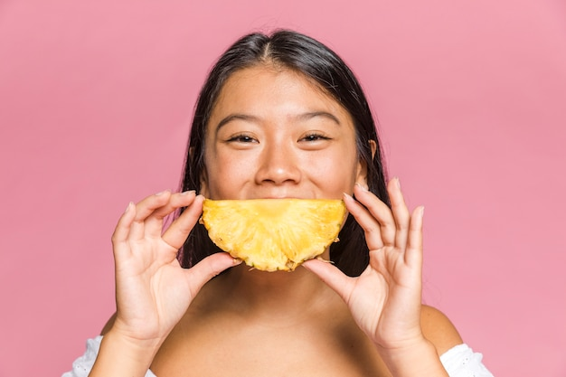 Woman holds a pineapple as a smiling shape Free Photo