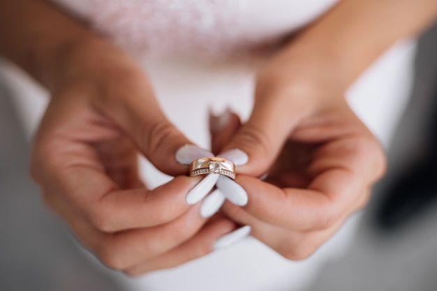 Woman holds precious wedding ring in her arms Free Photo