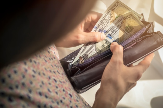 A woman holds a purse with money, dollars. Premium Photo