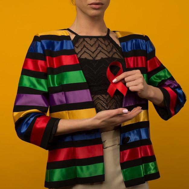 여자는 인식 세계 에이즈의 날 12 월 1 일에 빨간 리본을 보유 프리미엄 사진