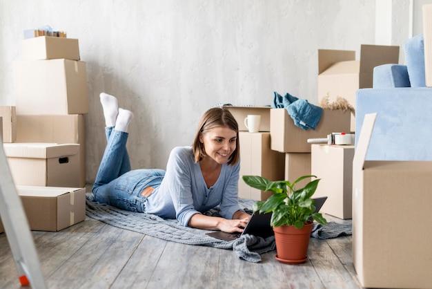 Donna a casa con scatole e pianta per uscire Foto Gratuite