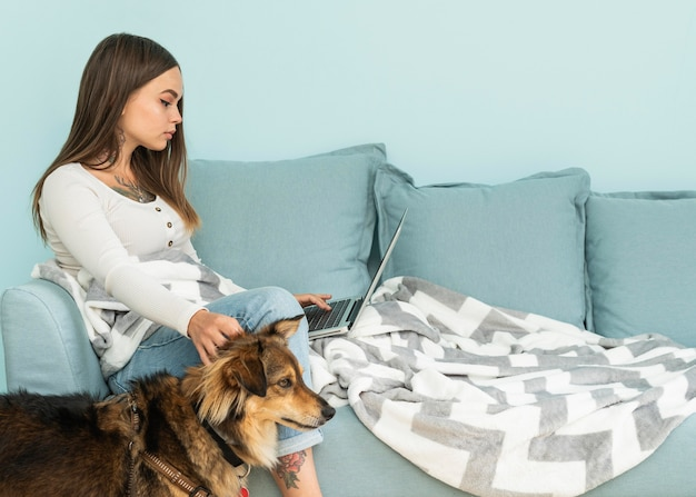 Donna a casa che lavora al computer portatile mentre accarezza il suo cane durante la pandemia Foto Gratuite
