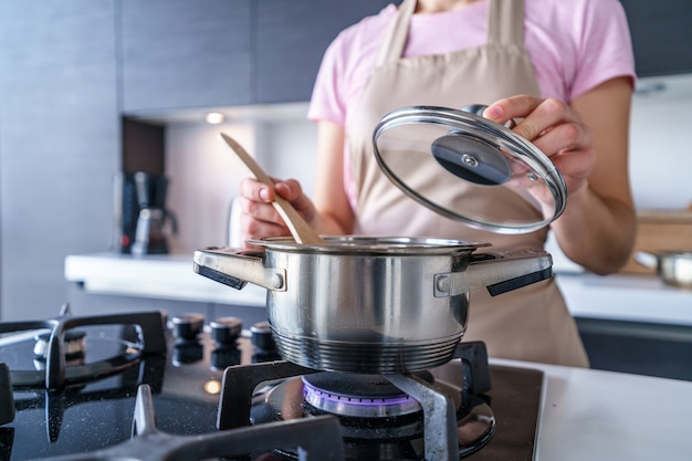 Woman housewife in apron using steel metal saucepan for preparing dinner in the kitchen at home. Premium Photo