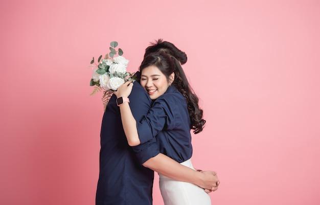 Woman hugging her boyfrienfd with bouquet in hand Premium Photo