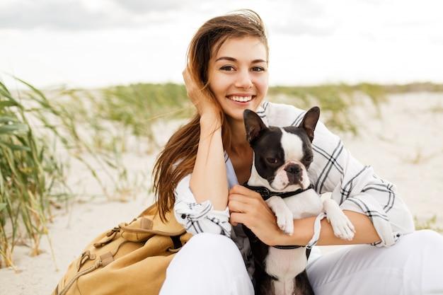 Donna che abbraccia il suo bulldog sulla spiaggia nella luce del tramonto, vacanze estive. ragazza alla moda con cane divertente che riposa, abbraccia e si diverte, momenti carini. Foto Gratuite