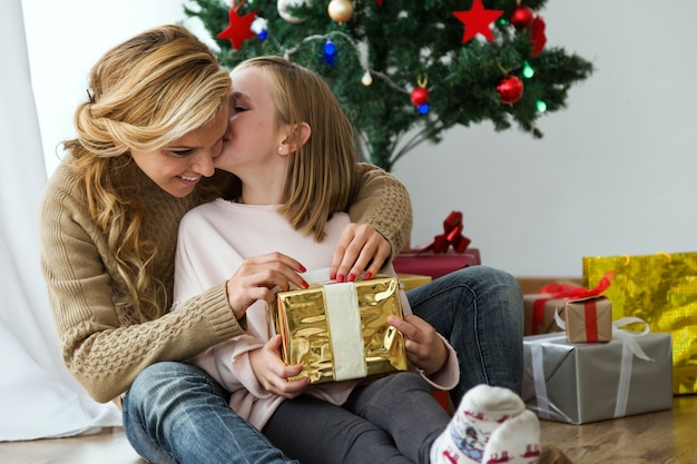 Woman Hugging Her Daughter With A Golden Gift And Gifts Background Free Photo