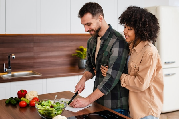 Woman hugging man cooking Free Photo