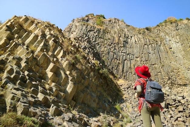 アルメニアのガルニ渓谷に沿った玄武岩の列の形成の信じられないほどの交響曲に感銘を受けた女性 Premium写真