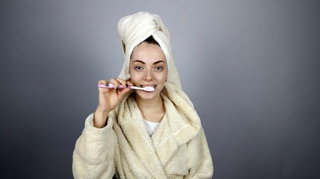 Женщина в халате чистит зубы Premium Фотографии