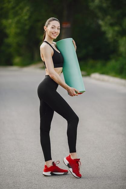 森の中に立っている黒いスポーツウェアの女 無料写真