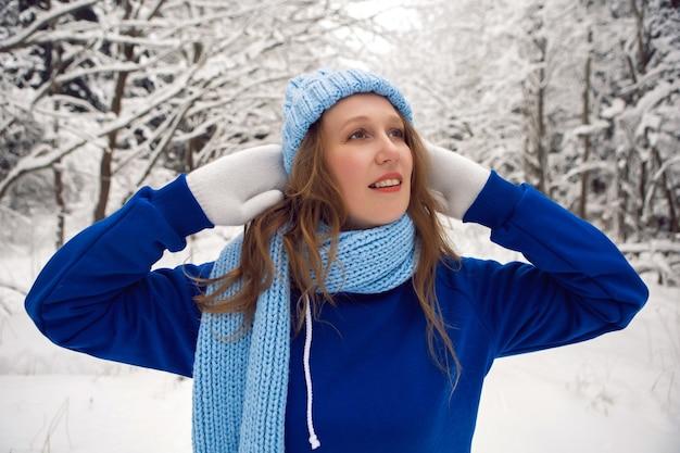 青いトラックスーツの白いミトンとスカーフの女性は、雪に覆われた森の冬に立っています Premium写真