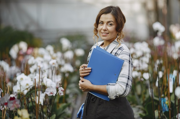 温室の女性。労働者は花をチェックします。フォルダを持つ女の子 無料写真
