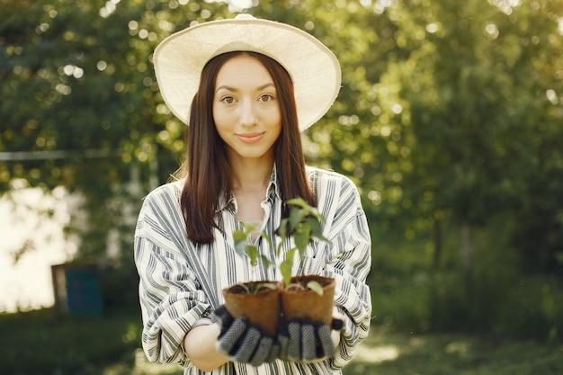 Женщина в шляпе держит цветочные горшки Бесплатные Фотографии
