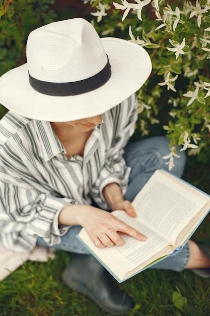 庭で本を帽子の女 無料写真