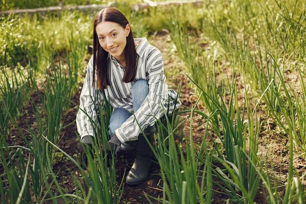 Женщина в шляпе работает в саду Бесплатные Фотографии