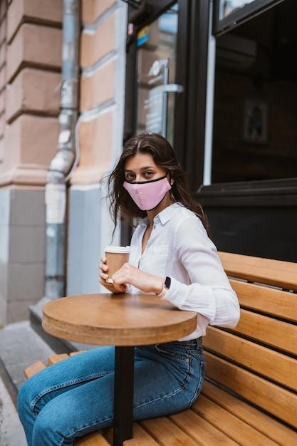 ウイルス感染を防ぐために医療マスクをかぶった女性が路上でコーヒーを飲む 無料写真