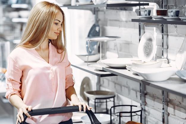 ピンクのブラウスを着た女性が店で料理を買う 無料写真