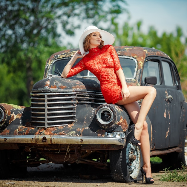 Woman in a red dress leaning against an old car Free Photo