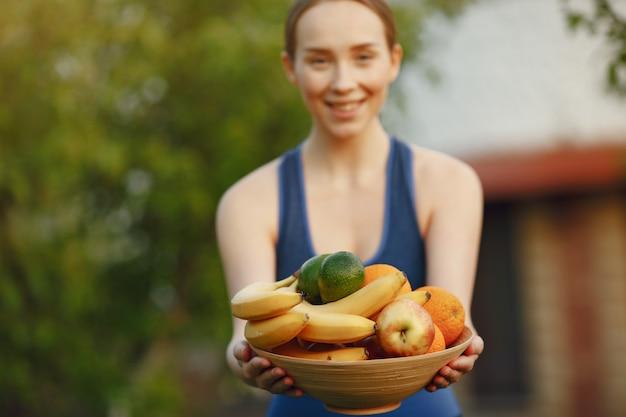 Женщина в спортивной одежде держит фрукты Бесплатные Фотографии