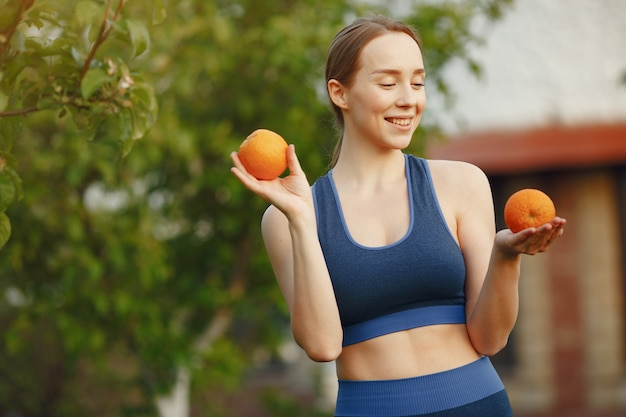 Sportwearの女性は果物を保持します 無料写真