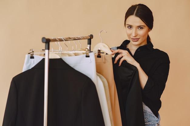 Женщина в студии с большим количеством одежды Бесплатные Фотографии
