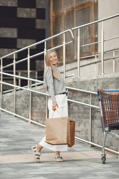 夏の街の女性。茶色のバッグを持つ女性。灰色のセーターを着た女性。 無料写真