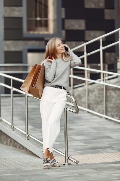 夏の街の女性。携帯電話を持つ女性。灰色のセーターを着た女性。 無料写真