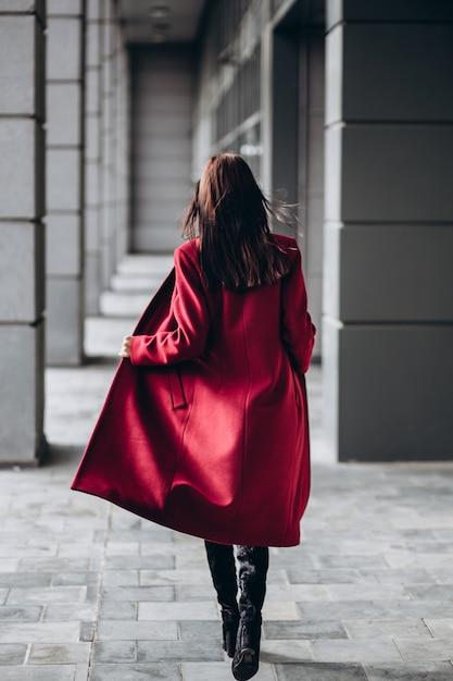 Женщина в теплом красном пальто на открытом воздухе Premium Фотографии