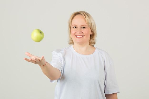 青リンゴと白いtシャツの女性 Premium写真