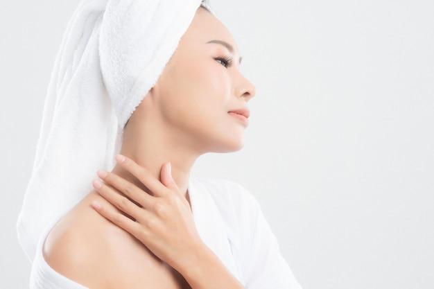 バスタオルを着た女性が彼女の顔に触れて、白で孤立して笑っています。 Premium写真