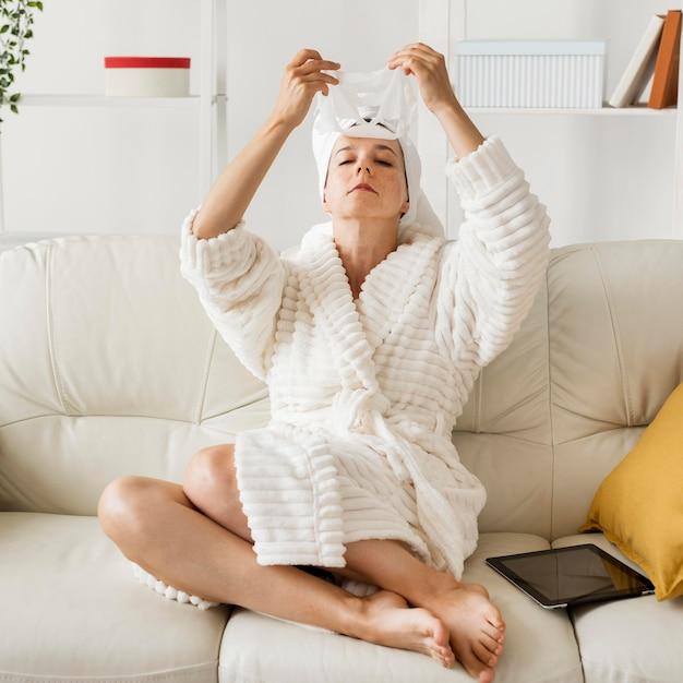 Женщина в халате, применяя маску для лица на диване Бесплатные Фотографии