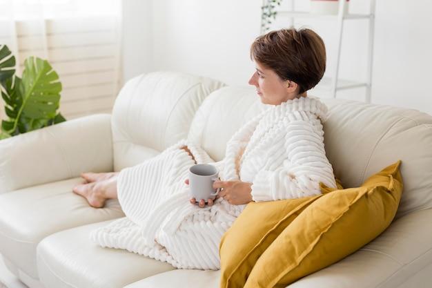 Женщина в халате держит чашку чая с длинным выстрелом Бесплатные Фотографии