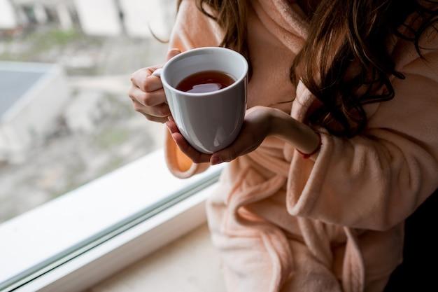 熱いお茶のカップを保持しているバスローブの女性。外気分。 無料写真