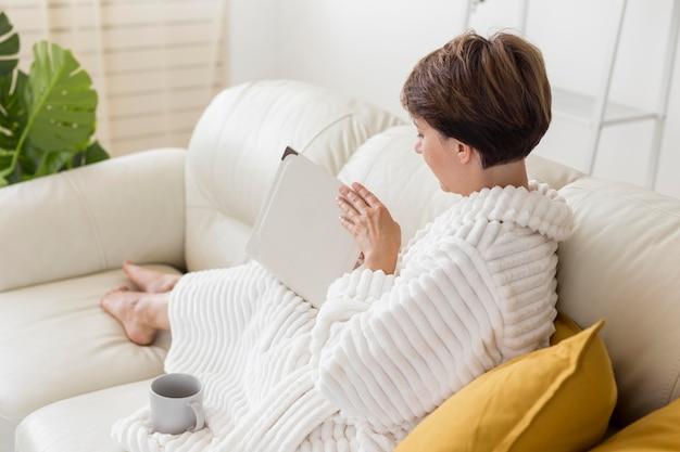 Женщина в халате, читая на диване Бесплатные Фотографии