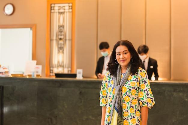 ホテルのフロントの前に立っている美しいドレスを着た女性。 Premium写真