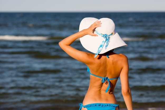 해변, 다시보기에 큰 모자에있는 여자 프리미엄 사진