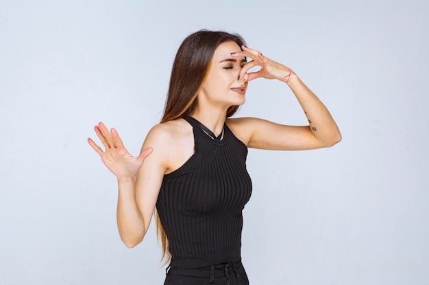 Женщина в черной рубашке чувствует неприятный запах. Бесплатные Фотографии