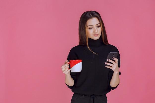 コーヒーカップを持って電話に話している黒いシャツを着た女性。 無料写真