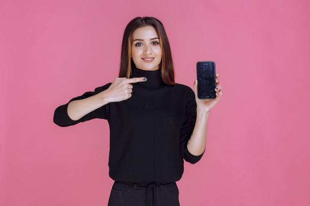 스마트 폰 들고 그것을 가리키는 검은 스웨터에 여자. 무료 사진