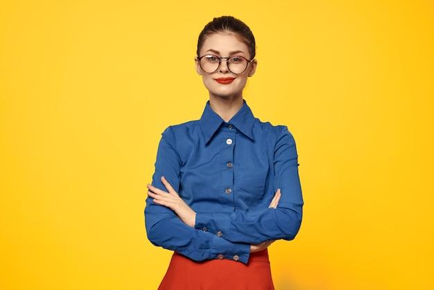 Женщина в синей рубашке и красной юбке очках на лице уверенный взгляд портрет желтый фон обрезанный Premium Фотографии