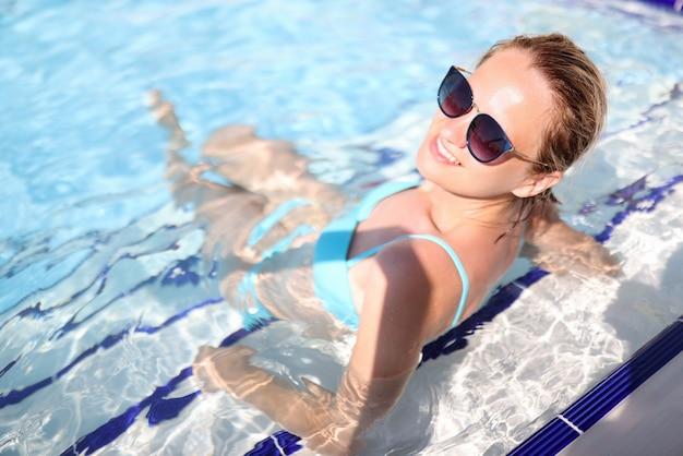 青い水着の女性がプールに座っています。 Premium写真