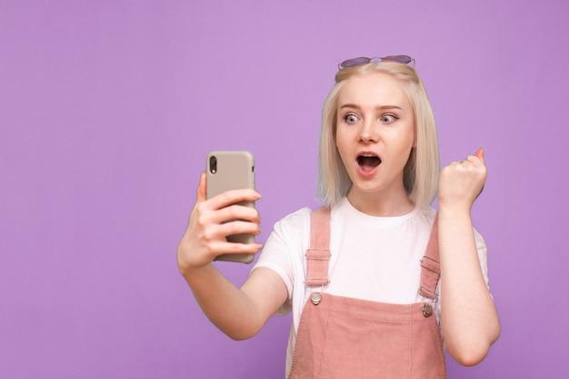 밝은 캐주얼 의류에 여자는 그녀의 손에 스마트 폰을 보유 프리미엄 사진