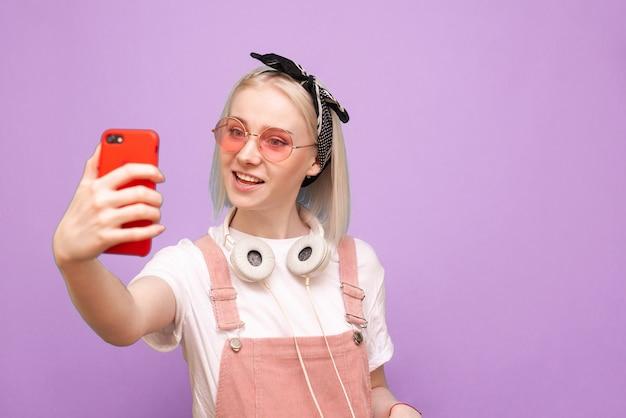 밝은 옷과 세련된 헤드폰을 입은 여성이 셀카와 미소를 짓습니다. 프리미엄 사진