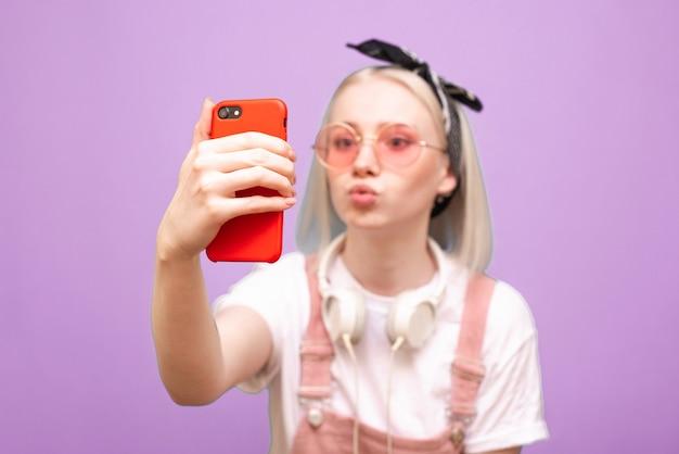 밝은 분홍색 안경에 여자는 재미있는 얼굴로 스마트 폰에 셀카를 걸립니다 프리미엄 사진